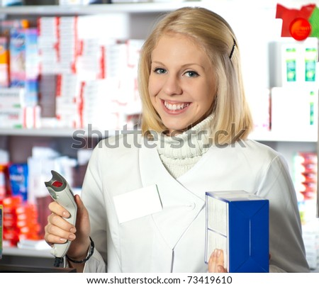 Cheerful pharmacist with barcode reader in hand.