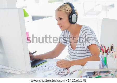 Cheerful photo editor working with graphics tablet at her desk - stock photo