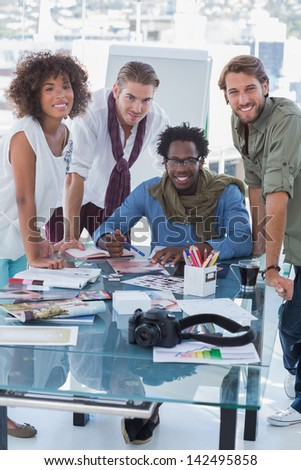 Cheerful photo editors in bright office looking at camera - stock photo