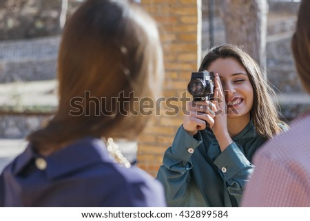 Cheerful photographer taking shot using vintage camera. - stock photo