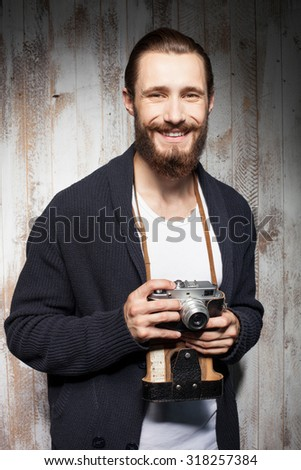 Cheerful photographer with beard is making photos. He is standing and smiling. The guy is looking forward happily - stock photo