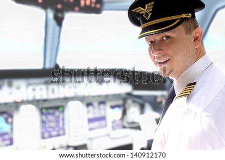 Cheerful pilot controls the aircraft in the cockpit - stock photo