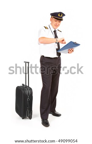 Cheerful pilot wearing uniform with epaulets standing with trolley bag and documents, checking time isolated on white background. - stock photo