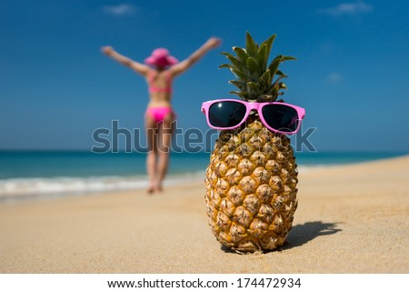 Cheerful pineapple glasses and a woman in a bikini sunbathing on the beach on sea background. Idealistic scene leisure travel. - stock photo