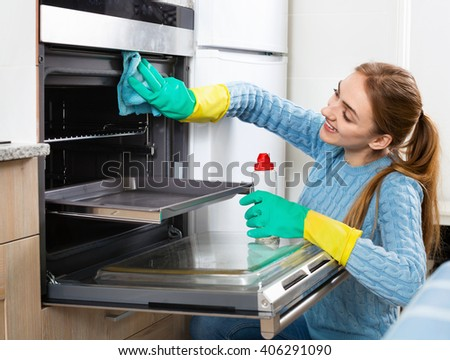 Cheerful positive adult girl in gloves removing snuff in oven  - stock photo