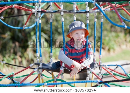 cheerful positive boy spending fun time at the playground - stock photo