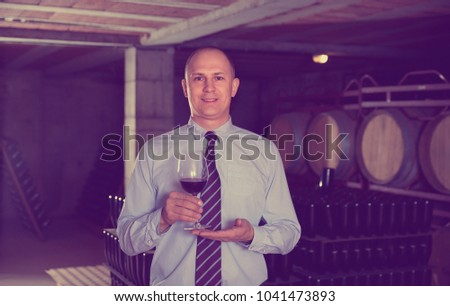 Cheerful positive glad male winemaker giving tour around winery, inviting to tasting red wine of own production