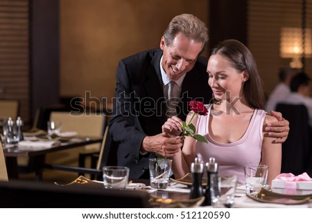 Cheerful positive man giving a rose to the woman