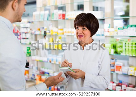 Cheerful  positive woman pharmacist in white coat helping customers to find item in drug store