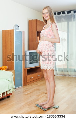 Cheerful pregnancy woman weighing herself on bathroom scale at home interior