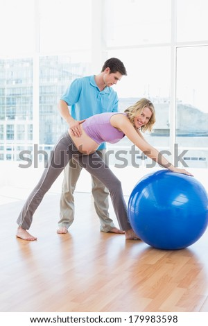 Cheerful pregnant woman exercising with trainer and ball in a studio