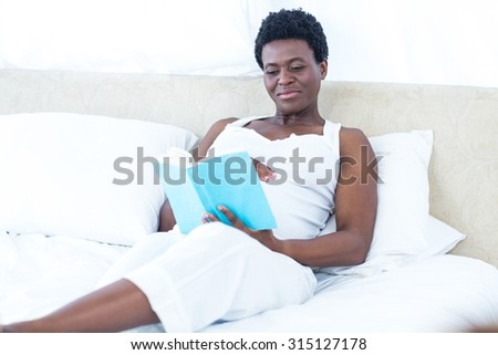 Cheerful pregnant woman reading book while relaxing on bed - stock photo