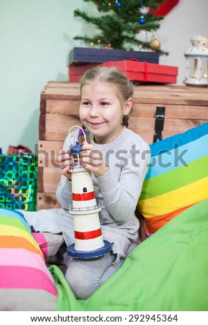 Cheerful preschool girl portrait, sitting with toy near the Christmas tree - stock photo