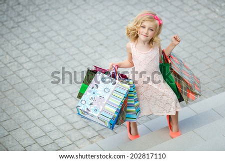 Cheerful preschool girl walking with shopping bags. Pretty smiling little girl with shopping bags with thumb up sign in the shop