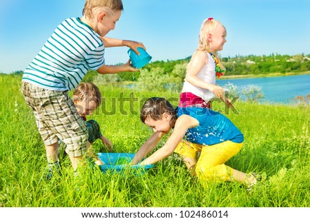 Cheerful preschoolers spreading water in the outdoors - stock photo