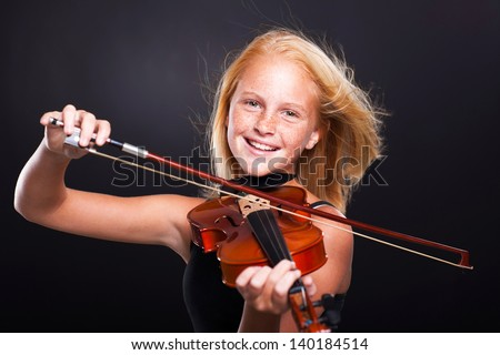cheerful preteen girl playing violin on black background - stock photo