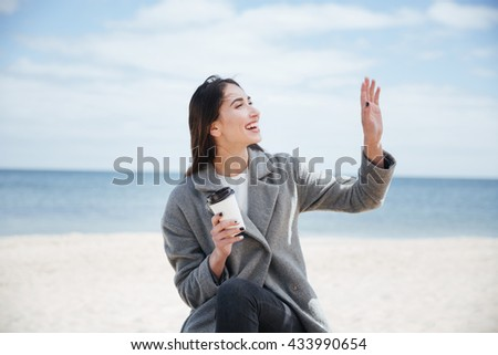 Cheerful pretty attractive woman waving to someoone and holding take away cup at the seaside - stock photo