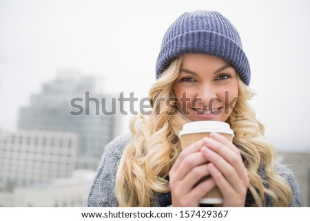 Cheerful pretty blonde having coffee outdoors on urban background