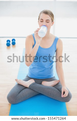 Cheerful pretty blonde in lotus position in bright sports hall drinking water - stock photo