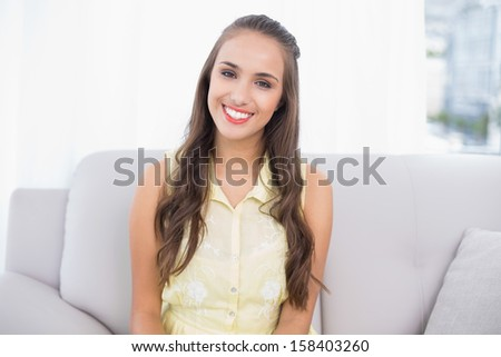 Cheerful pretty brunette sitting on coach in bright living room
