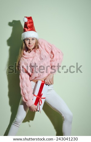 Cheerful pretty girl in Santa hat holding present