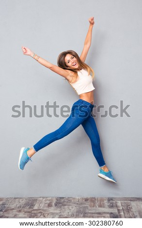 Cheerful pretty girl jumping over gray background. Looking at camera - stock photo