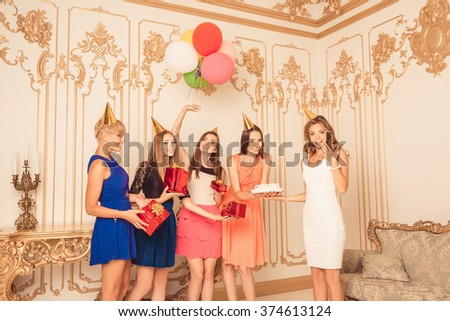 Cheerful pretty girls holding balloons and presents showing birthday cake - stock photo