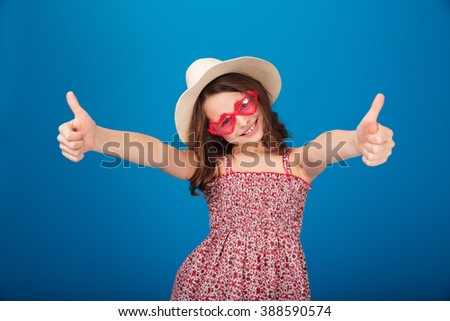 Cheerful pretty little girl in hat and heart shaped sunglasses  showing thumbs up over blue background - stock photo
