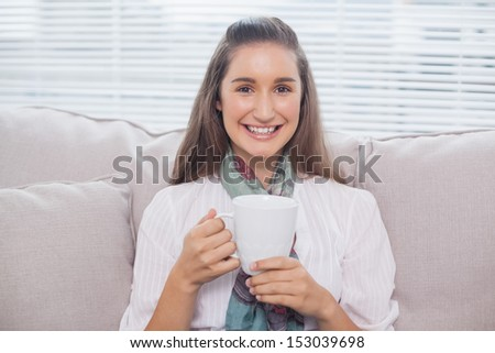 Cheerful pretty model holding cup of coffee sitting on cosy sofa