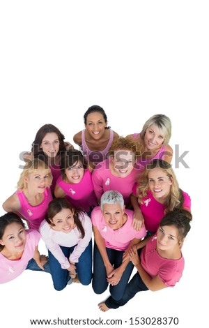 Cheerful pretty women looking up wearing pink for breast cancer on white background - stock photo