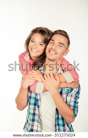 Cheerful pretty young woman embracing her boyfriend - stock photo