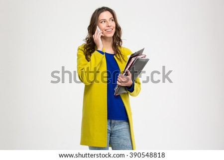 Cheerful pretty young woman holding folders with documents and talking on cell phone over white background - stock photo