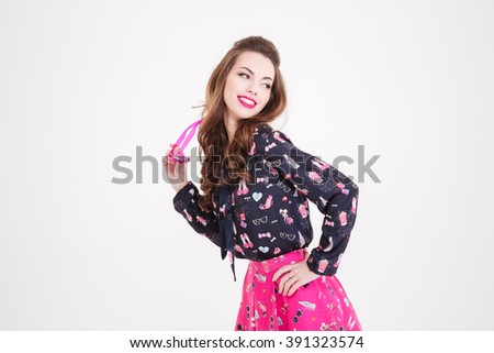 Cheerful pretty young woman holding sunglasses and posing over white background  - stock photo