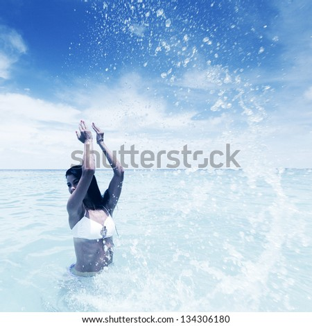 Cheerful pretty young woman splashin in sea - stock photo