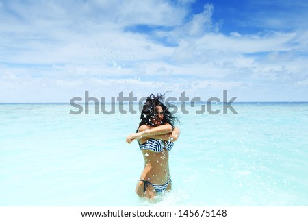 Cheerful pretty young woman splashin in sea - stock photo