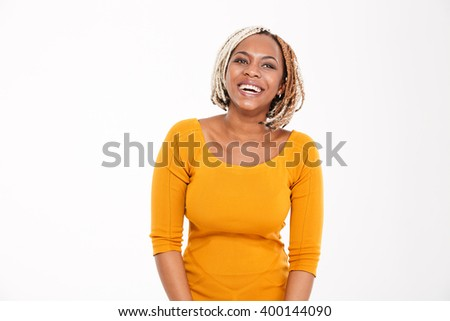 Cheerful pretty young woman standing and laughing over white background - stock photo