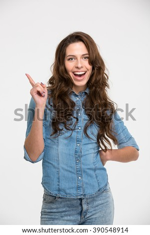 Cheerful pretty young woman standing and pointing away over white background - stock photo