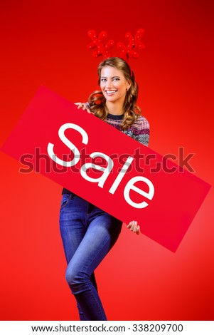 Cheerful pretty young woman wearing Christmas deer horns holding sale board. Beauty, fashion. Shopping. - stock photo
