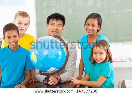 cheerful primary school geography teacher and students with a globe