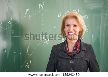 Cheerful professor standing in front of a chalkboard - stock photo