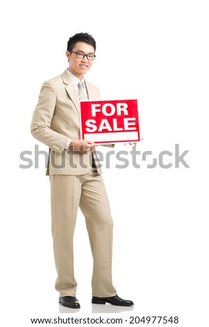 Cheerful real estate agent holding for sale signboard - stock photo