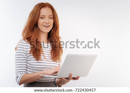 Cheerful red-haired woman holding a laptop