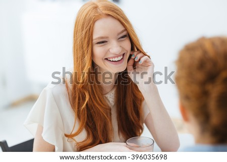 Cheerful redhead pretty young woman sitting and laughing with her friend in cafe - stock photo
