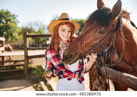 Cheerful redhead young woman cowgirl giving food to horse on ranch