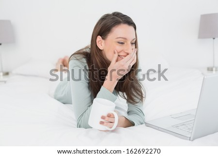 Cheerful relaxed casual young woman with laptop and cup in bed at home - stock photo