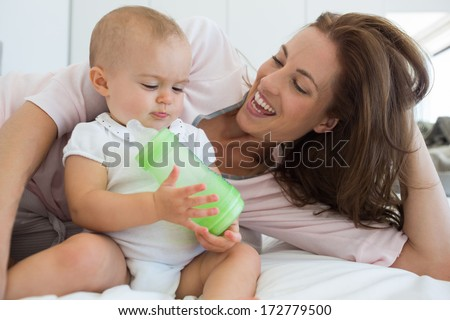 Cheerful relaxed mother with baby holding milk bottle on bed at home - stock photo