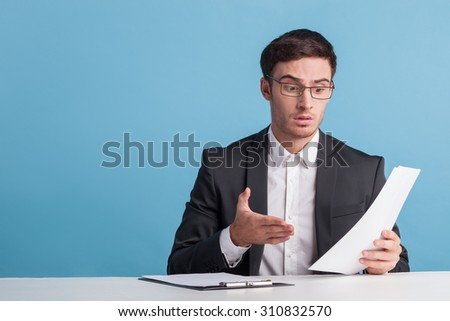 Cheerful reporter is sitting at the table and holding papers. The man is looking at it with surprise. He is gesturing emotionally. Isolated on blue background and copy space in left side - stock photo