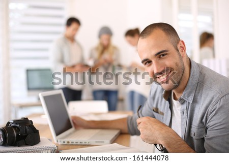 Cheerful reporter working in office on laptop - stock photo