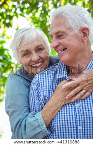 Cheerful retired couple hugging while standing outdoors - stock photo