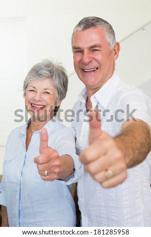 Cheerful retired couple looking at camera giving thumbs up at home in living room - stock photo